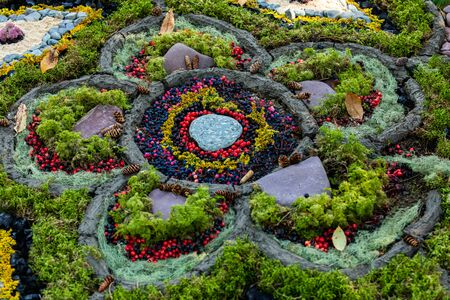 A close up shot of creative floral art made of colorful foraged items from a forest, large flower pattern with green moss, red winterberries, foliage