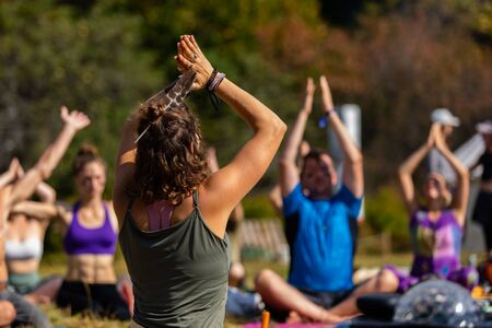 A healthy yoga instructor with bronzed skin is seen from behind in shallow focus, holding hands in a prayer position during a guided class in nature Stock fotó