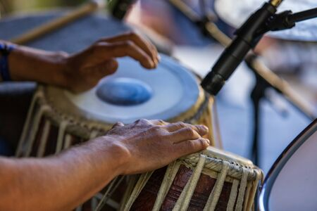A close up selective focus shot on the hands of a drummer playing traditional Madal, Maadal, drums during a folk music set at a multicultural festival