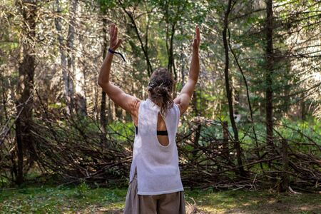 A fit caucasian woman is seen from behind with muscular toned arms raised in air during tai chi martial arts routine, in woodland with blurry trees in background
