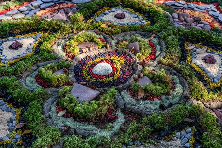 A closeup and high angled view of colorful natural art pattern, flower shape from forest berries, foliage, rocks. Art in woods at earth festival 스톡 콘텐츠