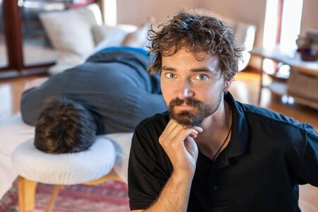 Portrait of middle-aged physical therapist posing with lying and waiting for massage male patient. Front view of a professional masseuse Archivio Fotografico