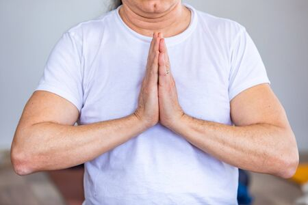 The man clasped his hands in a yoga pose. A man in a white makes a yoga exercise. The man in the white t-shirt in prayer pose Foto de archivo