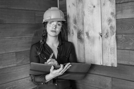 attractive and elegant worker caucasian woman wearing a hard hat and protective eyewear and holding a clipboard. female architect, inspector concepts