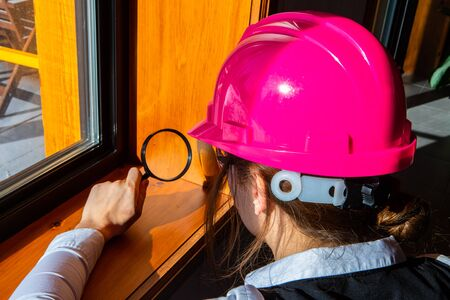 close up on woman inspector using a magnifying glass during air quality inspection, looking for molds or fungi problems on the wooden window edges