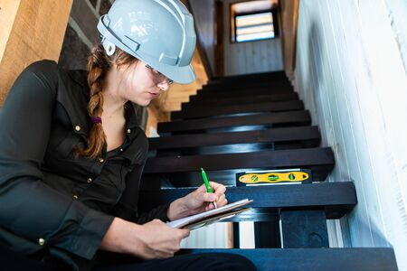 worker woman sitting on a stair taking professional notes on her clipboard. female inspector reviews house stairs surface with a spirit level. Stockfoto