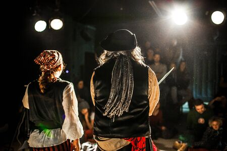 An atmospheric shot on stage during a pirate show in a theater by night with actors in costume and blurry audience in background, copy space to right.