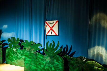 A french sign saying treasure with a big red cross, x marks the spot, on stage during a pirate show at a theater with green and blue decoration and copy space.