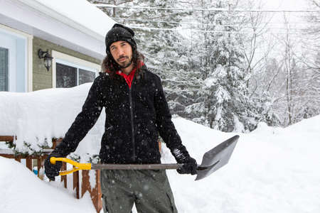 Man in his thirties standing outdoor holding a shovel. house and trees covered with snows during snowfall in background. snow shoveling and removing.