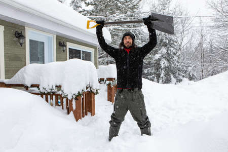 Happy and excited young man smiling as he standing outdoor holding up a shovel for manual snow removal, house and trees covered by snow in background.