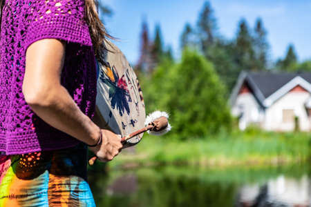Close up on the arms of a young woman on the shore of a Canadian lake holding a native leather hand painted drum or tambourine and a clapper.