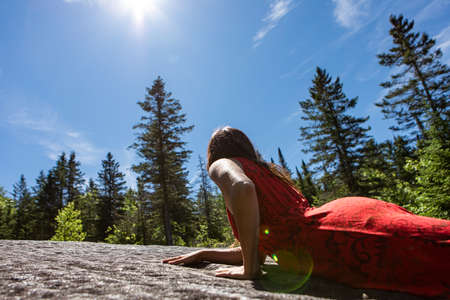 Young long haired woman in a sleeveless bright red city dress lying on a rock in the middle of the Canadian woods. Connecting with nature. Sun flares.