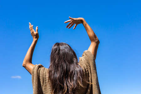 Close up from behind of a woman in a brown crochet poncho sweater with her hands up in the air in a ritual, tribal energy dance or movement.