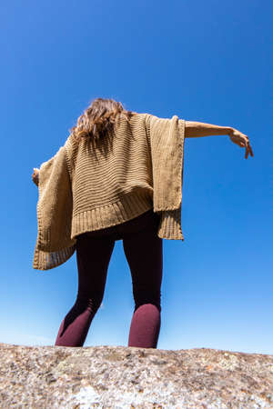 Rear view from below of a woman in a brown crochet poncho sweater against a bright blue sky,dancing a ritual, tribal energy dance.