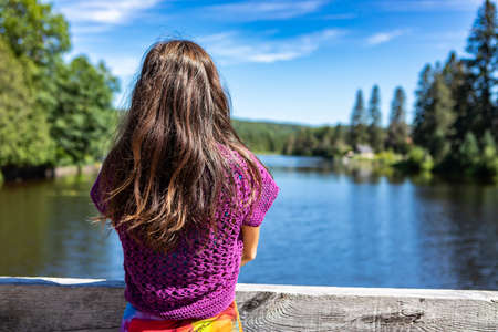 View from behind of a slender young woman in a purple crochet top standing on a parapet on a Canadian lake with her arms folded on her chest.