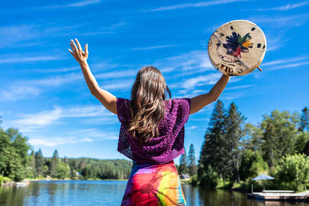 Young woman acting a ritual dance on the shore of a lake, raising her hands to the sky with a native leather hand painted drum or tambourine.