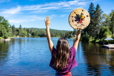 Young woman acting a ritual dance on the shore of a Canadian lake holding a native leather hand painted drum or tambourine in her raised hands. Banque d'images