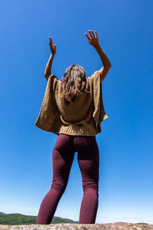 Rear view from below of a woman in a brown crochet poncho sweater against a bright blue sky, hands up in the air in a ritual, tribal energy dance.