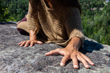 Long haired woman in a brown crochet poncho sweater on a hilltop overlooking a Canadian forest, hands up in the air in a ritual, tribal energy dance.