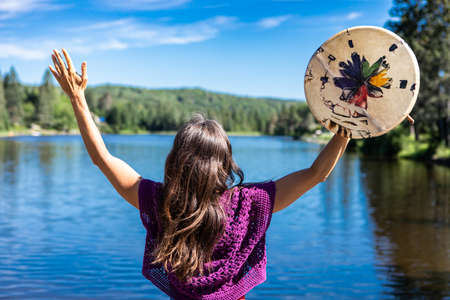 Young woman on the shore of a Canadian lake raising her hands in the air, and holding a native leather hand painted drum or tambourine