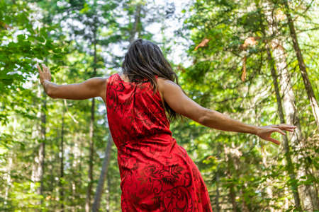 View from behind of a slender young woman in a red dress dancing a ritual energetic dance in the middle of the woods, with her arms wide open.