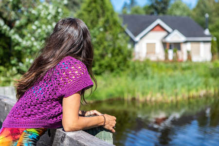 Slender young woman in bright purple crochet top leaning on a wooden parapet overlooking a lake and a house in the blurred background. Warm summer day