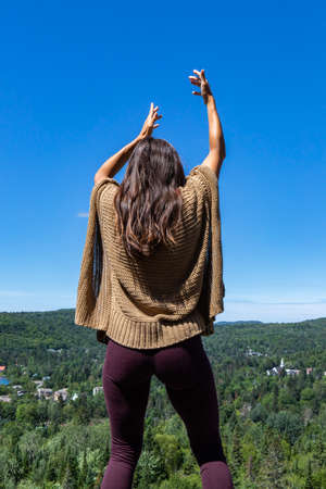 Long haired woman in a brown crochet poncho sweater on a hilltop overlooking a Canadian forest, with her hands up in a ritual, tribal energy dance.