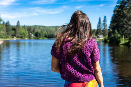 View from behind of a slender young woman in a purple crochet top standing on the shore of a lake. Bright sunny day, warm canadian summer.