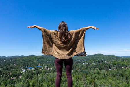 Rear view of a long haired woman in a brown crochet poncho sweater on a hilltop overlooking a Canadian forest, hands up in the air. Bright blue sky.