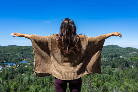 Long haired woman in a brown crochet poncho sweater on a hilltop overlooking a Canadian forest, hands up in the air. Bright blue sky.