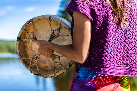 Close up on the arms of a young woman on the shore of a Canadian lake holding a native leather hand painted drum or tambourine in her hand. Banque d'images