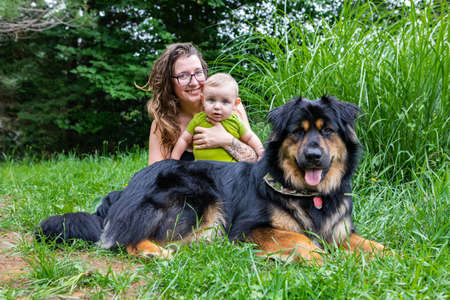Mommy, baby son and big black furry dog posing for camera in outdoor portrait. Mommy smiling and holding her baby while they all look at camera.