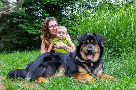 Mommy, baby son and big black furry dog posing for camera in outdoor portrait. The three of them looking at camera, mommy smiling and holding her baby