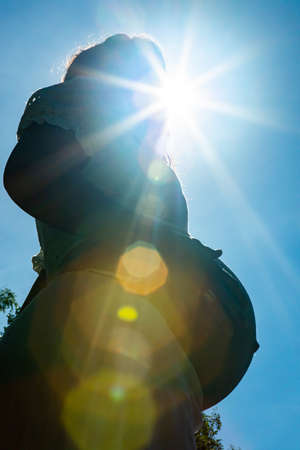 Backlit close up, from below, of the big belly of a pregnant woman during a bright sunny day. Sun star and beautiful sun flares and bokeh effect. Verti Banque d'images