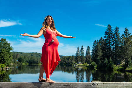 Young pregnant woman in a sleeveless red dress walking on the parapet of a lake and stretching arms open for balance. Canadian lake background. Banque d'images