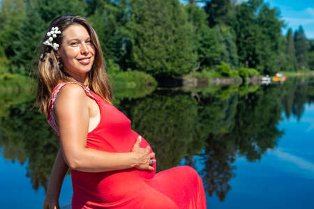 Portrait of a pregnant woman in a sleeveless red dress sitting on the parapet of a lake above the water, caressing her belly and smiling at camera.