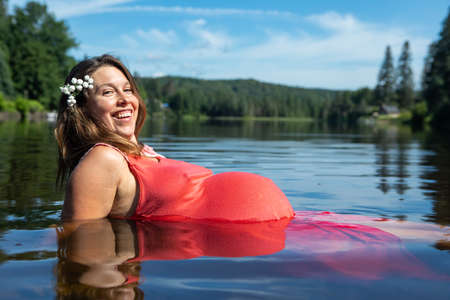 Beautiful pregnant young woman in a sleeveless red dress sitting with her big belly in the water of a canadian lake and smiling at camera.
