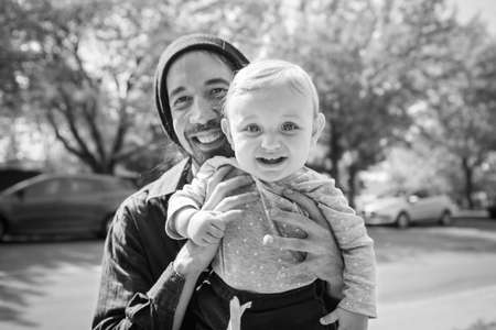 Portrait of happy young and handsome father, holding cute little infant baby in hands while playing in outdoor street in a black and white frame