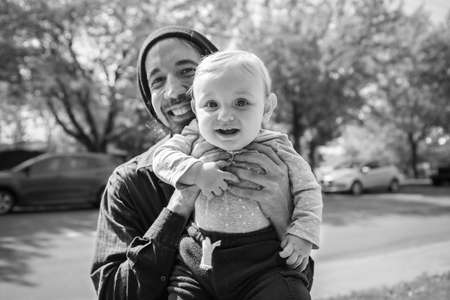 Black and white portrait of cute little baby boy in casual clothing, being held by father while playing in outdoor street in a village of Quebec