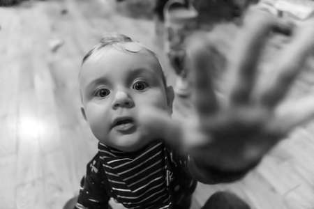 Black and white portrait shot of playful and curious little cheeky baby boy, playing at home while stretching hand forwards towards camera as to grab it 写真素材