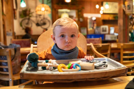 Cute little infant baby boy playing with his educational wooden toy of all colors and shapes, in winter clothing while looking with surprise at camera