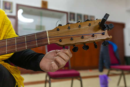 Selective focus of male hands tuning guitar strings during dia de los muertos, also known as, day of the dead, during ceremony