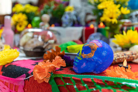 Beautiful and fresh campasuchil decorated on stand with sugar skull in altar during celebration of dia de los muertos in mexico with illuminated candle
