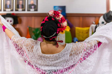Rear view of young beautiful female performing with open arms in front of decor of skull, dolls and campasuchil flower in altar during day of the dead