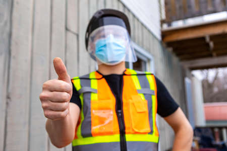 selective focus. Close up of man with orange and yellow fluo visibility jacket, covid protective face mask and plastic visor giving the thumbs up sign