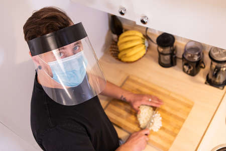 Close up shot from above of a young man in the kitchen, chopping an onion on a cutting boar wearing covid protective face mask and plastic visor
