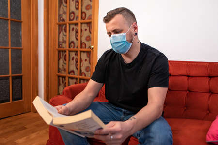 Exaggerated covid prevention. Man reading a book on a red couch, wearing a protective sanitary mask against covid. Ironic shot, exaggerated prevention