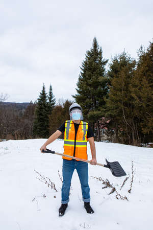 Wide angle view of a man wearing an orange fluo visibility jacket over a t-shirt, covid protective face mask and plastic visor, shoveling the snow 写真素材