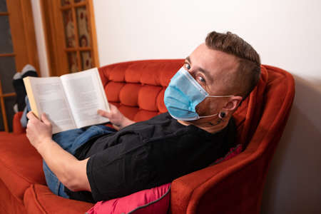Exaggerated covid prevention. Man looking at camera while reading on a red couch wearing protective sanitary mask against covid. Ironic shot.