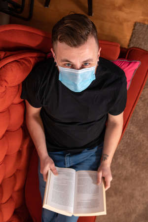 Exaggerated covid prevention. View from above of man looking up at camera while reading on a couch with protective mask against covid. Ironic shot.